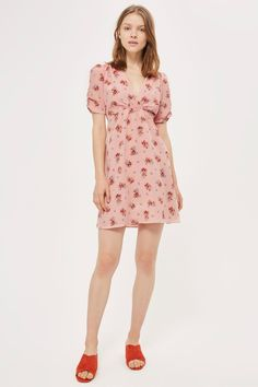 In a pretty shade of blush pink, this graceful floral tea dress will be an instant favourite. Falling above the knee, this floaty number comes with ruched short sleeves, a v-neckline, and shirred detailing to the chest. Finish this look with strappy sandals and a vintage-look handbag.