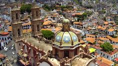 """Taxco de Alarcón is a small city located in the Mexican state of Guerrero. The name Taxco is most likely derived from the Nahuatl word tlacheco, which means """"place of the ballgame."""" However, one interpretation has the name coming from the word tatzco which means """"where the father of the water is,"""" due to the high waterfall near the town center on Atatzin Mountain. """"De Alarcón"""" is in honor of writer Juan Ruiz de Alarcón who was a native of…"""