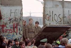 Die Mauer bricht, Segment für Segment: DDR-Grenzsoldaten schauen auf ein Meer...