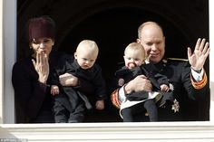 Princess Charlene of Monaco blows a kiss to the crowds as she holds onto Prince Jacques, w...