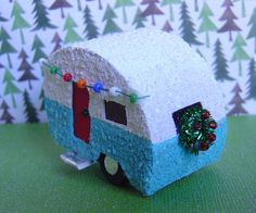 Putz style glitter Christmas camper trailer:  How cute is this?!? This cute little turquoise and white colored trailer is just 2 1/4 inches in length, and stands just 1 5/8 inches in height. Features include cellophane windows, wooden wheels, sparkling glitter finish and a tiny wreath and string of lights.