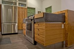 Brindle Strand Bamboo Cabinets with rough tile backsplash, concrete countertops, and stainless steel appliances