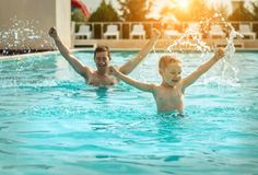 Father and son funny in  water pool under sun light at summer da