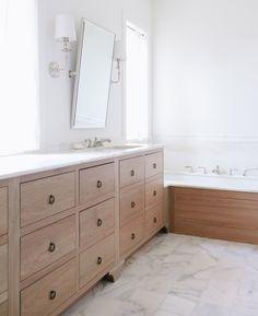 Light wash wooden drawer vanity in master bathroom   Jean Stoffer Design