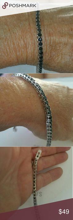 black saphire  tennis bracelet silver setting tennis bracelet with black saphires stones set into bracelet double lock clasp. beautiful bracelet. rcvd as a gift. Wore a few times.(I already have a tennis bracelet so I didn't wear this much Jewelry Bracelets