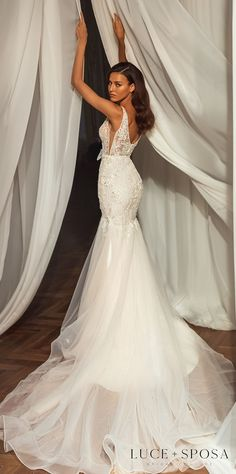 Beautiful lace mermaid wedding dress style with deep v-neckline, bow belt, dramatic cape and tulle trumpet skirt | Luce Sposa Wedding Dresses 2021- Kinsley - Belle The Magazine #weddingdress #weddingdresses #bridalgown #bridal #bridalgowns #weddinggown #bridetobe #weddings #bride #dreamdress #bridalcollection #bridaldress #dress See more gorgeous bridal gowns by clicking on the photo