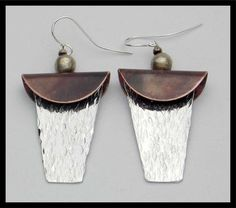 Bold and dramatic! Hand cut from copper and pewter sheet. Copper circles were flamed with torch to darken and folded in half. Pewter was hammered to produce lots of texture. Earrings are about 2 3/4 inches in length, inc handforged sterling french wires.