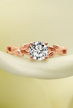 Wispy vines and delicate buds of rose gold entwine toward a brilliant center diamond in this nature-inspired ring.