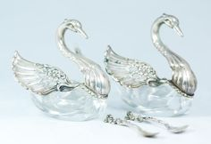 Pair of German silver and crystal figural swan salt cellars. Each has a reticulated design with hinged wings that can be adjusted to cover the salt cellars.