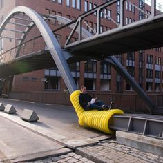 "Urban studies 101: if you let them sit, they will come. This is the delightfully simple concept behind Oliver Show's ""Street Furniture,"" a series of guerilla public seating areas that sprouted into being through the wrapping of yellow drainage pipes around Hamburg's existing urban infrastructure. The low-cost, weather-resistant and highly flexible plastic cushions turn bridge trusses into recliners, bike racks into loungers, and safety rails into sofas."