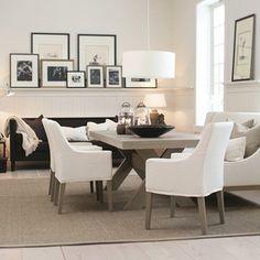 Matplats rustikt bord, vita stolar, tavelvägg