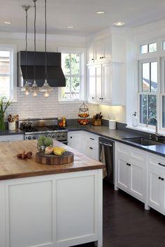 White cabinet, bronze knobs, dark counter top, dark wood floor, stainless steel appliances