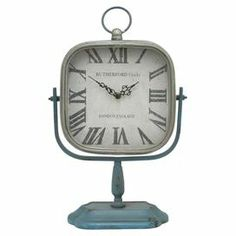 "Bring antiqued style to your home office or living room with this charming vintage-inspired table clock, featuring a weathered blue finish.   Product: Table clockConstruction Material: MetalColor: Silver and blueFeatures: Weathered finishAccommodates: Batteries - not includedDimensions: 11.5"" H x 8"" W"