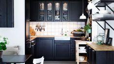 Cuisine noire Ikea - Encore une fois, il n'y a pas de mal à opter pour un agencement plus classique. Les cuisines en U sont en effet tout aussi efficaces. Cette pièce est ainsi meublée d'éléments brun noir METOD, finition LAXARBY, avec tablettes et portes vitrées. Sans oublier le meuble d'angle et le mobilier pour évier DOMSJÖ. L'évier est d'ailleurs encastré entre deux plans de travail. Le tout est complété par une desserte en bouleau BEKVÄM et un éclairage de cuisine adapté.