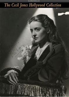 """Bette Davis - Signed oversize photograph. (ca. 1940s) Vintage original gelatin silver double-weight 10.4 x 13.25 in. trimmed glossy production portrait of Davis by Six from All This, and Heaven Too inscribed and signed, """"Neil, Bette Davis"""". Photo retains photographer's inkstamp and paper studio snipe on the verso."""