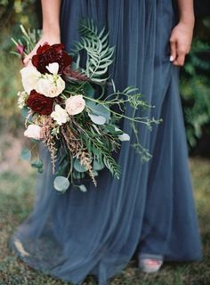 Loose unstructured bouquet with oxblood pops of colour and steel grey blue tulle bridal or bridesmaids skirt