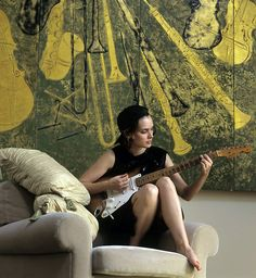 Winona Ryder playing guitar in her apartment by Joe McNally, 1994
