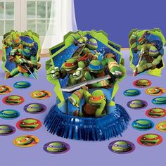 "You'll be a hero for sure when you decorate with this Teenage Mutant Ninja Turtles Table Decorating Kit! The kit includes one large centerpiece that has a fringe base and measures 12.5""""H, two smaller"