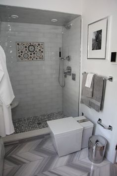 Contemporary bathroom in Philadelphia, PA. Love the tile inset in the shower and the herringbone pattern tile on the floor. Note the Kohler numi toilet.