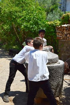Some children grind the grain as in ancient times, Lotzorai, Ogliastra
