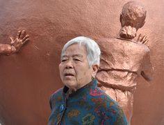Una mujer posa delante de un monumento por la reunificación de Corea del Norte y del Sur.