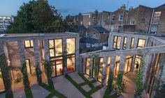 The homes face a shared multifunctional courtyard landscaped with a geometric pattern of resin-bound gravel and grass strips laid out to look like a ground-plane extension of the brick columns.