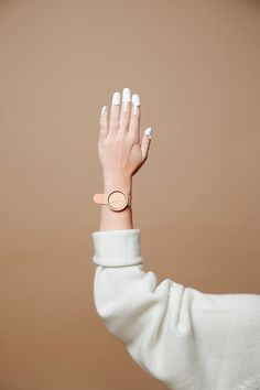 Searching for source ? Clean peach and white fashion shot for a watch. Painted fingers.