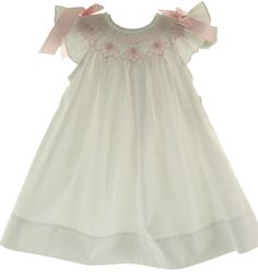 Baby girls white angel bishop dress with pink smocking and pink satin bows on the shoulder.  Hiccups Childrens Boutique - Bow Peep Infant Girls White Smocked Angel Bishop Pink Smocking