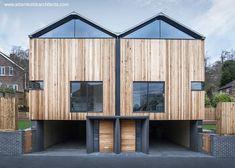 Casas gemelas inglesas contemporáneas, de madera, sobre un podio oscuro de concreto.