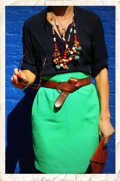 Fabulous grouping of colorful necklaces ove a navy blouse belted with the green skirt worn by blogger, Lucy Laucht. via sfgirlbybay.com.