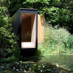 This wooden folly cantilevering across a garden lake creates a meditation room and children's play den.