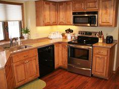 Kitchen - cabinets refaced in Maple with medium brown walnut stain.  Balterio laminate floor in dark cherry.