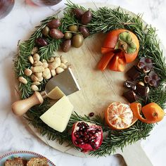 Holiday Wreath Cheese Plate --- rosemary, cheese, mandarins, persimmon, pomegranate, nuts, olives, dark chocolate, crackers.--- Place the rosemary around the a plate or wooden or slate cheese board to create a wreath shape. Top with all the other ingredients. Christmas.