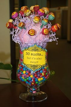 My friend Amy and I came up with a cute center piece for a 30th birthday gift. We took a glass vase filled it with candy (jelly beans and m...