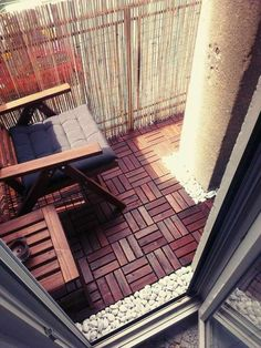 revêtement de sol en bois composite et galets blancs, chaise en bois avec galette grise et table basse en bois sur le balcon