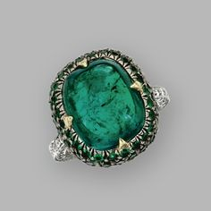 EMERALD AND DIAMOND RING. The cushion-shaped antique pyramidal cabochon emerald weighing 8.82 carats, framed by round emeralds, flanked by round diamonds weighing approximately .70 carat, mounted in gold and platinum