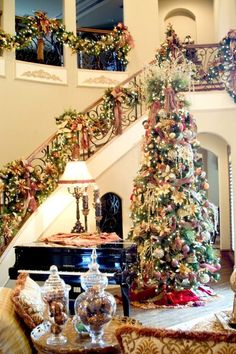 Amazing luxurious Christmas decoration with elegant high Christmas tree filled with lots of beautiful ornaments and stunning staircase handrails decor. ~ 50 Stunning Christmas Staircase Decorating Ideas - Style Estate