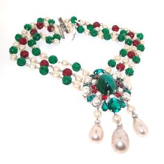 A Stunning classic Christian Necklace date 1960 featuring emerald and ruby coloured glass and glass pearls in a triple strand with centre piece. Necklace length measures 18 - 2- inches. Centre piece measures 9.5cm drop by 5cm wide. The 3 strands are 3cn deep in total.  Our shop is in London, Portobello Road, International shipping is with FEDEX.