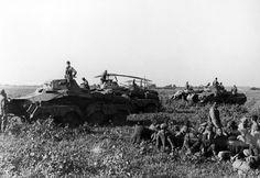 German Schwerer Panzerspähwagen reconnaissance vehicles with a group of Soviet prisoners, 1942.