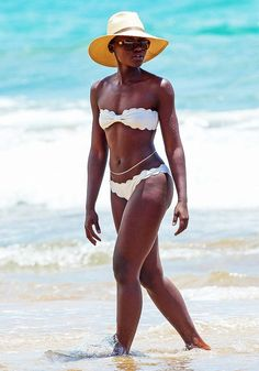 Lupita Nyong'o wears a white scalloped hem bandeau top with matching scalloped bottoms, a straw hat, and sunglasses.