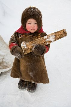 A 2 year old komi girl helps to carry firewood at her family's winter camp | yamal, northwest siberia, Russia
