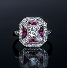 A Superb Vintage Art Deco Ruby Diamond Platinum Ring, Russian, Circa 1930. The ring is crafted in platinum over 18K gold and centered with an oval old cut diamond in a milgrain platinum setting framed by calibre cut synthetic rubies and old single cut diamonds.