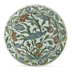 AN INTACT IZNIK POTTERY DISH OTTOMAN TURKEY, CIRCA 1620 On short flat foot, with sloping rim, the decoration on white ground with carnations and tulips, a saz leaf across the center, the rim with palmettes and five-petalled rosettes, intact 11½in. (29.3cm.) diam.