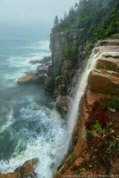 Waterfalls coming off of otter cliffs during storm at Acadia national park, USA