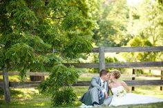 bride and groom kissing near a wooden fence in the country   Photo: Janelle Elise Photography