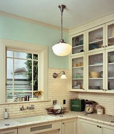 kitchen with penny tile countertop, subway tile, cream and seafoam paint, and schoolhouse light - more of my favorite things! (via green bicycle)
