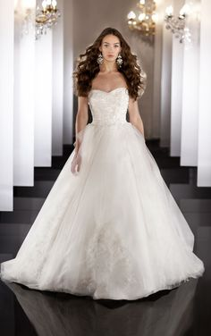 Silk and tulle designer bridal gown features Swarovski Crystals and hand embroidery detail throughout the bodice, and layered within the flowing tulle skirt. Covered buttons.