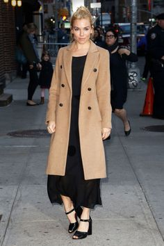 Sienna Miller broke up her all-black ensemble with a structured camel coat that pulls together a night-out look, whether over a cocktail dress or sultry separates.