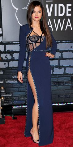 At the MTV Music Video Awards, Selena Gomez pulled out all the stops in a long-sleeve navy Atelier Versace gown with a studded trim, thigh-high slit and bustier. She styled her look with matching pumps and emerald Lorraine Schwartz danglers.