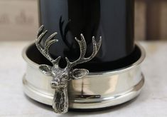 """Stag Bottle Coaster £34.00  A great example of a beautiful and original item which would grace any table or homeware collection. This pewter bottle coaster features a hand cast pewter stag and will not rust or tarnish. Supplied with its own cream and black presentations box. H1.2"""" x 3.8"""" Dia."""